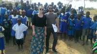 Dr. Jaime Meza-Cordero​ and Ms. Lauren Lochocki on site in Malawi surrounded by schoolchildren.